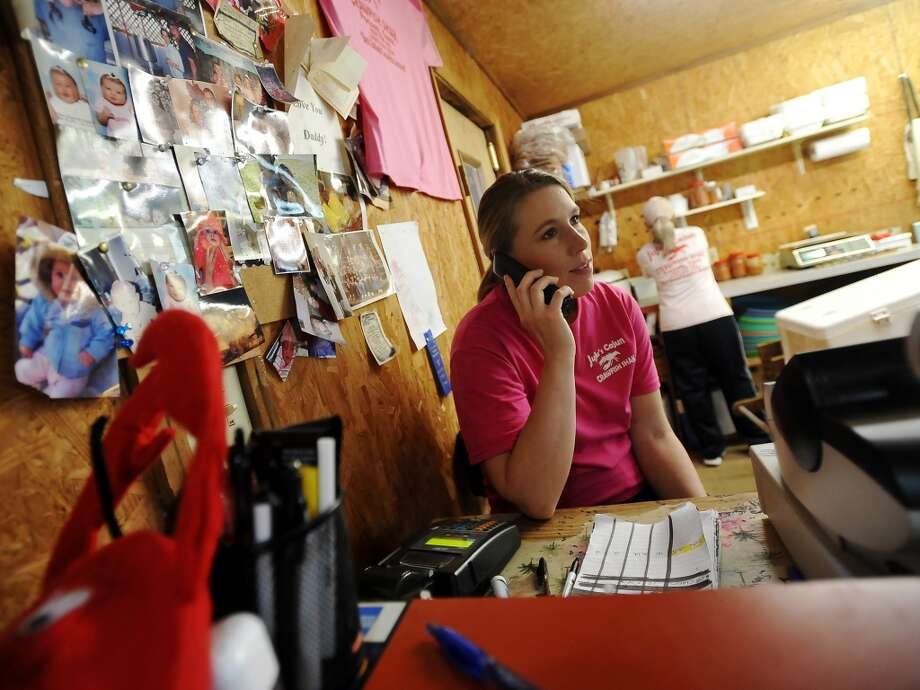 Lacy Carter answers the phone at the small counter space at JuJu's Cajun Crawfish on Thursday. The Fannett restaurant serves up nothing but crawfish, corn on the cob, and potatoes during the mudbug season. The small, family-owned restaurant is in its 12th year. Photo taken Thursday, 2/27/14 Jake Daniels/@JakeD_in_SETX