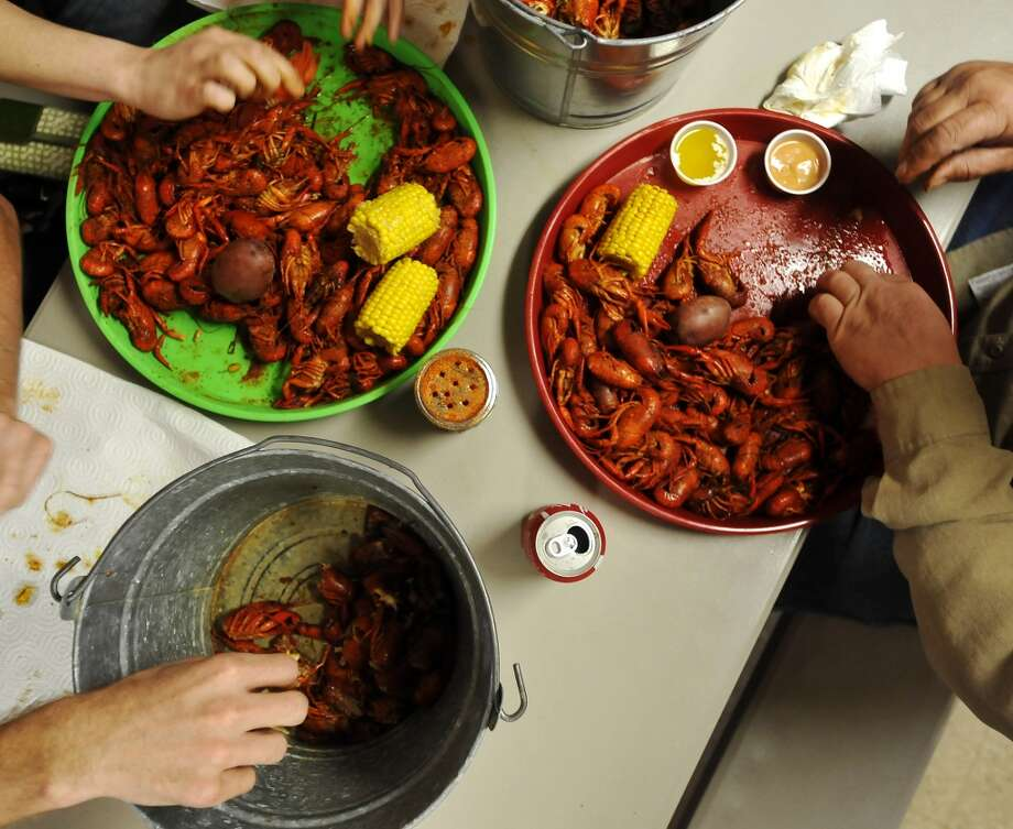 Bryson Brittain, Amber Pounds, and Wes Pounds dig into a few pounds of crawfish Thursday afternoon. JuJu's Cajun Crawfish in Fannett serves up nothing but crawfish, corn on the cob, and potatoes during the mudbug season. The small, family-owned restaurant is in its 12th year. Photo taken Thursday, 2/27/14 Jake Daniels/@JakeD_in_SETX