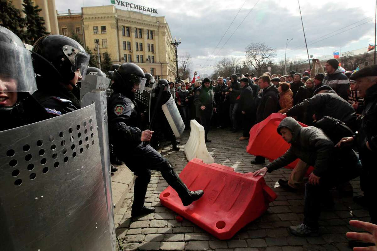 A Ukrainian riot police officer tries to prevent a pro-Russia demonstrator from picking up a road block near the regional administrative building during a rally at a central square in Kharkiv, Ukraine, Sunday, March 16, 2014. Thousands of pro-Russia demonstrators gathered in Ukraine's northeastern town of Kharkiv to show their support for the Crimean referendum.