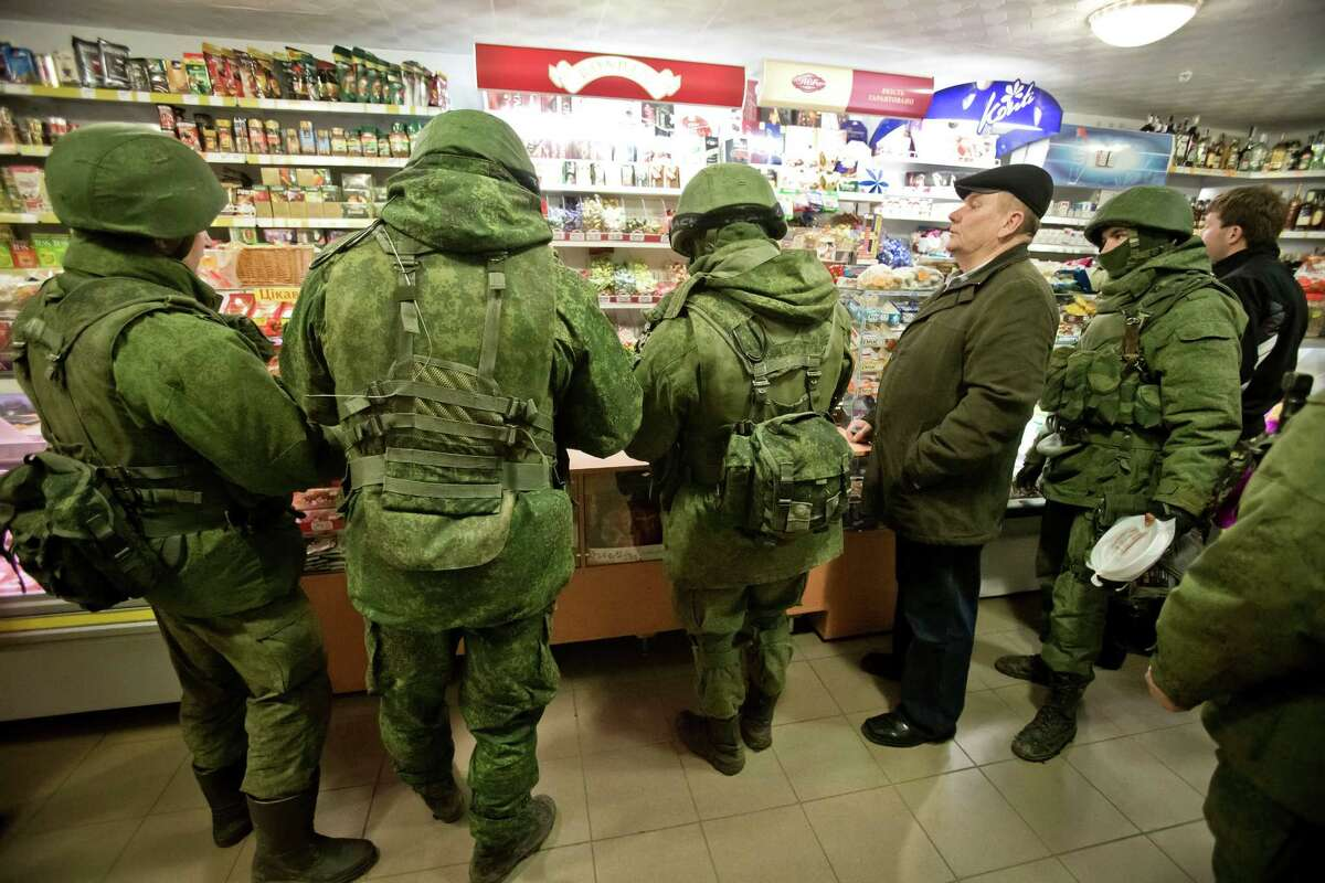 Masked unidentified soldiers and local residents are seen inside a shop in Perevalne, Ukraine, Sunday, March 16, 2014. In a referendum watched closely around the world, residents in Ukraine's strategic Crimean Peninsula voted Sunday on whether to demand greater autonomy or split off and seek to join Russia. The vote has been condemned as illegal by the United States and European countries.