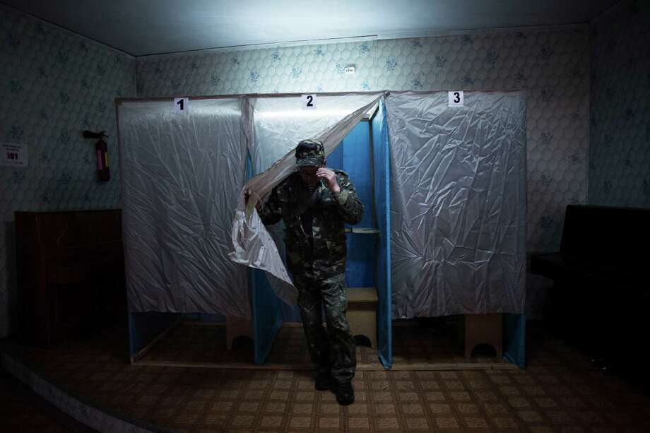 A Ukrainian man, member of a pro Russia self defense unit walks out of the voting cabin in Bachisaray, Ukraine, Sunday, March 16, 2014.  In a referendum watched closely around the world, residents in Ukraine's strategic Crimean Peninsula voted Sunday on whether to demand greater autonomy or split off and seek to join Russia. The vote has been condemned as illegal by the United States and European countries. Photo: Manu Brabo, AP / AP