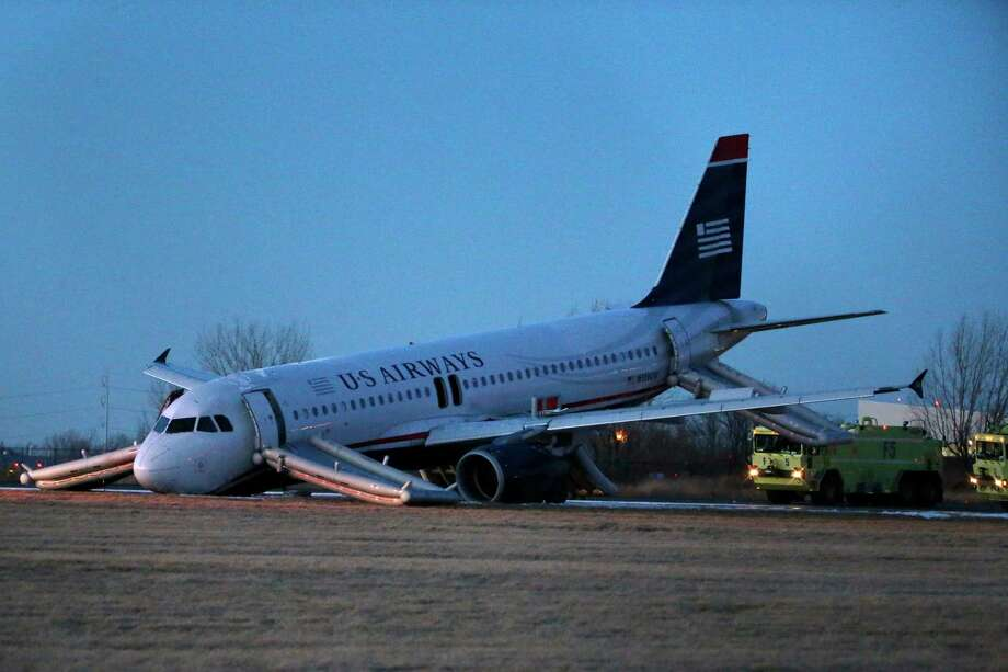 A damaged US Airways jet lies at the end of a runway at the Philadelphia International Airport, Thursday, March 13, 2014, in Philadelphia. Airline officials said the flight was heading to Fort Lauderdale, Fla., when the pilot was forced to abort takeoff around 6:30 p.m., after the front landing gear failed. An airport spokeswoman said no injuries have been reported. Photo: Matt Slocum, AP / AP2014