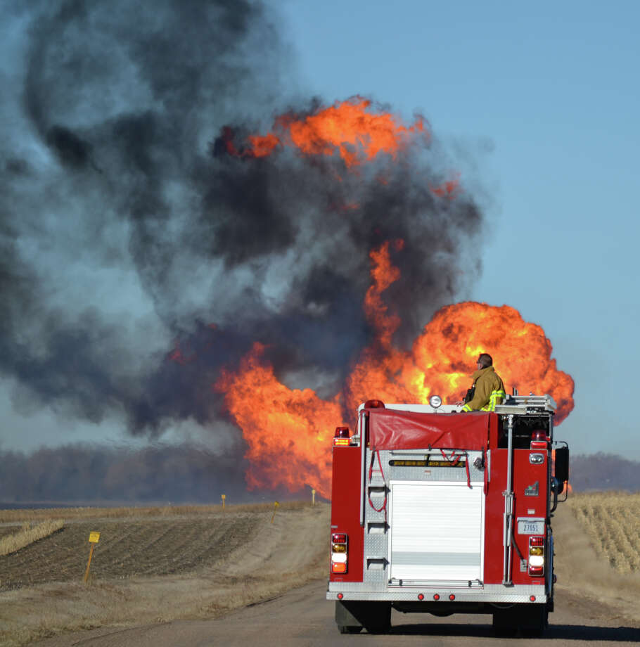 A Nickerson firefighter watches the flames from a natural gas pipeline fire on Friday, March 14, 2014  north of Fremont.  The line erupted about 8:30 a.m. Friday near the intersection of county roads 20 and O, about six miles north of Fremont. No damage to any structures has been reported. Firefighters from four departments were waiting nearby for workers to turn off the gas flow. The flames towered dozens of feet into the sky, and the heat kept firefighters from getting close enough to see what caused the blast. Photo: Chris Zavadil, AP / The Tribune