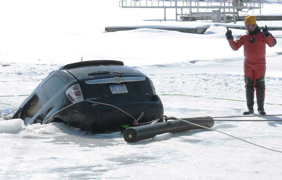 Rich Lenardson, owner of Great Lakes Repair and Great Lakes Tow BoatU.S., directs a crane operator as they remove a vehicle from the ice at Paw Paw Lake in Coloma, Mich., Friday, March 14, 2014. According to police, a 46-year-old woman drove through a yard, around a wood dock, over a concrete barrier and onto a frozen channel early Wednesday morning. The driver escaped and was booked for operating while intoxicated and placed in the Berrien County Jail. A field sobriety test indicated her blood-alcohol level was 0.18 percent, more than twice the legal limit. Photo: DON CAMPBELL, AP / The Herald-Palladium