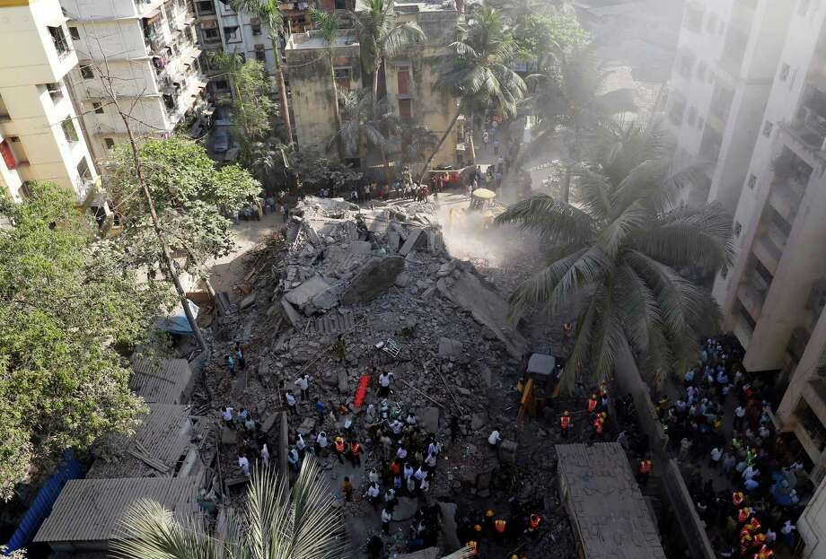 Rescue workers search for survivors in the debris of a building that collapsed in Mumbai, India, Friday, March 14, 2014. An old, seven-story residential building collapsed Friday in a Mumbai suburb, killing at least two people and possibly trapping more under the debris, Indian officials said. Photo: Rajanish Kakade, AP / AP2014