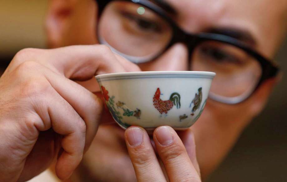 "A staff member from Sotheby's presents the Meiyintang ""Chicken Cup"" from the Chinese Ming Dynasty (1368-1644) during the media preview for the auction of Fine Art Chinese Ceramics and Works of Art sales in Hong Kong, Wednesday, March 12, 2014. The cup is expected to fetch HK$200-300 million (US$25.6-38.5 Million). Photo: Kin Cheung, AP / AP2014"