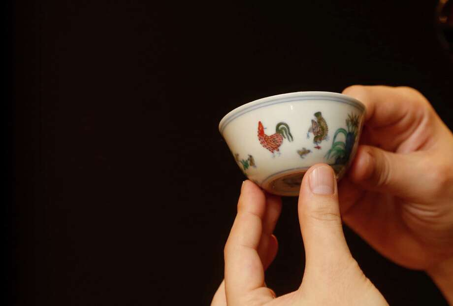 "A staff member from Sotheby's holds the Meiyintang ""Chicken Cup"" from the Chinese Ming Dynasty (1368-1644) during the media preview for the auction of Fine Art Chinese Ceramics and Works of Art sales in Hong Kong, Wednesday, March 12, 2014. The cup is expected to fetch HK$200-300 million (US$25.6-38.5 Million). Photo: Kin Cheung, AP / AP"