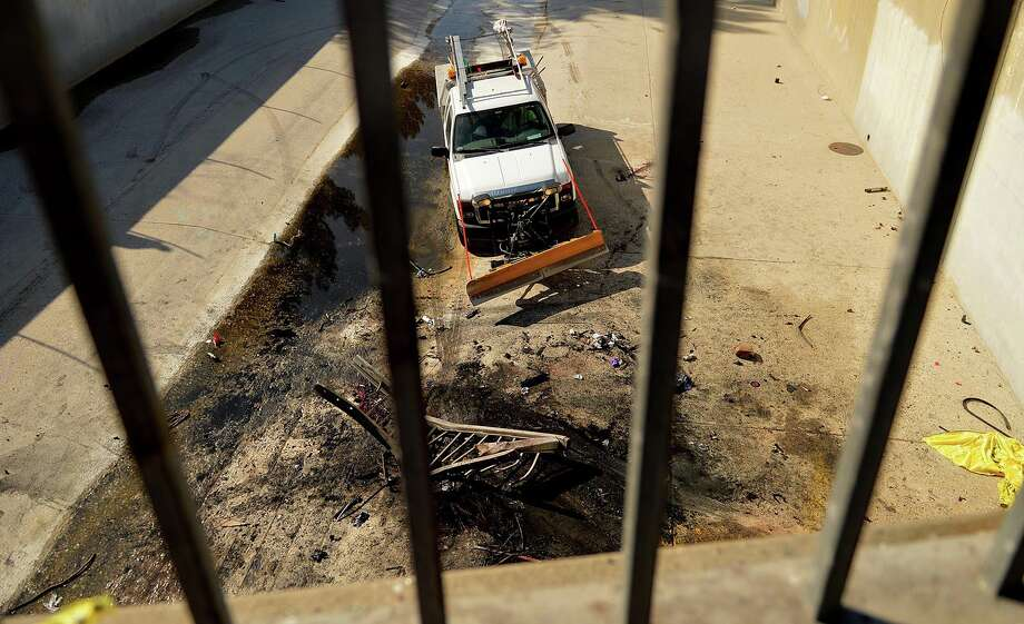 A San Bernardino city worker clears debris from the scene of a fatal accident Friday March 14, 2014 at E 5th Street near Cooley Avenue in San Bernardino, Calif. A speeding car carrying four women veered out of control, smashed through a metal bridge railing, plunged 20 feet into a concrete wash and burst into flames, killing everyone, authorities said Friday. (AP Photo/The Sun, LaFonzo Carter)  Photo: LaFonzo Carter, AP / The Sun