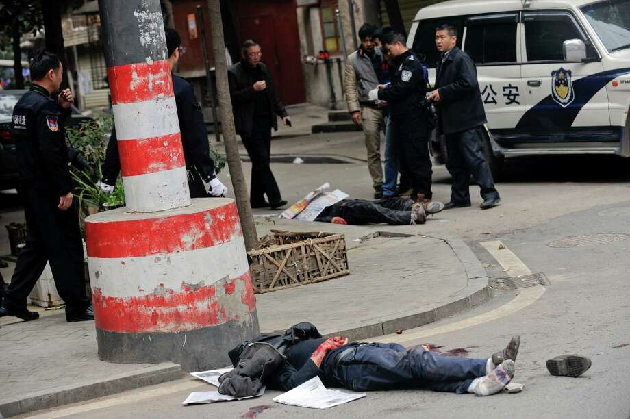 Bodies of victims lie on the ground as policemen investigate the crime scene after a knife attack in Changsha, in southern China's Hunan province, Friday, March 14, 2014. A fight between two food stall owners at a market in southern China on Friday left five people hacked to death and one person fatally shot by police, authorities said. The identity of the food stall owners was not immediately clear.  (AP Photo)  Photo: AP / CHINATOPIX