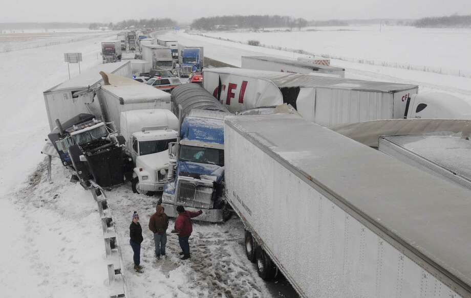 Truck drivers talk amongst themselves at the scene of an accident on the Ohio Turnpike, northeast of Clyde, Ohio, after more than 50 vehicles crashed, Wednesday, March 12, 2014. Photo: Jonathon Bird, AP / AP2014