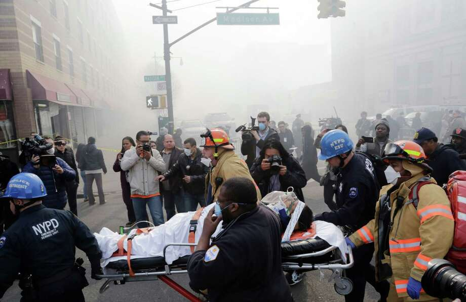 Rescue workers remove an injured person on a stretcher after a possible explosion and building collapse in the East Harlem neighborhood of New York, Wednesday, March 12, 2014 Photo: Mark Lennihan, AP / AP2014