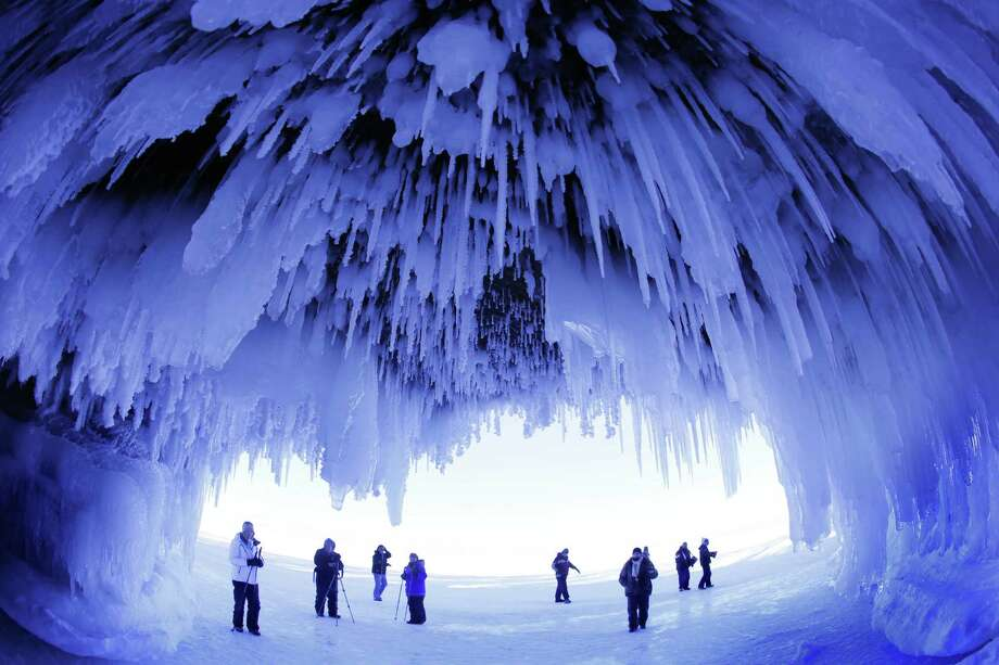 The popular ice caves on Lake Superior will soon be closed due to ice melt, according to the Apostle Islands National Lakeshore Superintendent. The caves are usually accessible only by water, but Lake Superior's rock-solid ice cover is letting people walk to them for the first time since 2009. In this Feb. 2, 2014 photo, people visit the caves at Apostle 