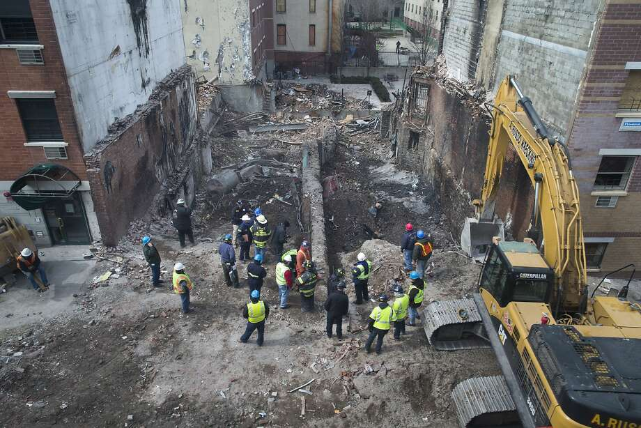 Workers gather after rubble is cleared from the basements of the two buildings leveled by a blast Wednesday in New York. Photo: John Minchillo, Associated Press