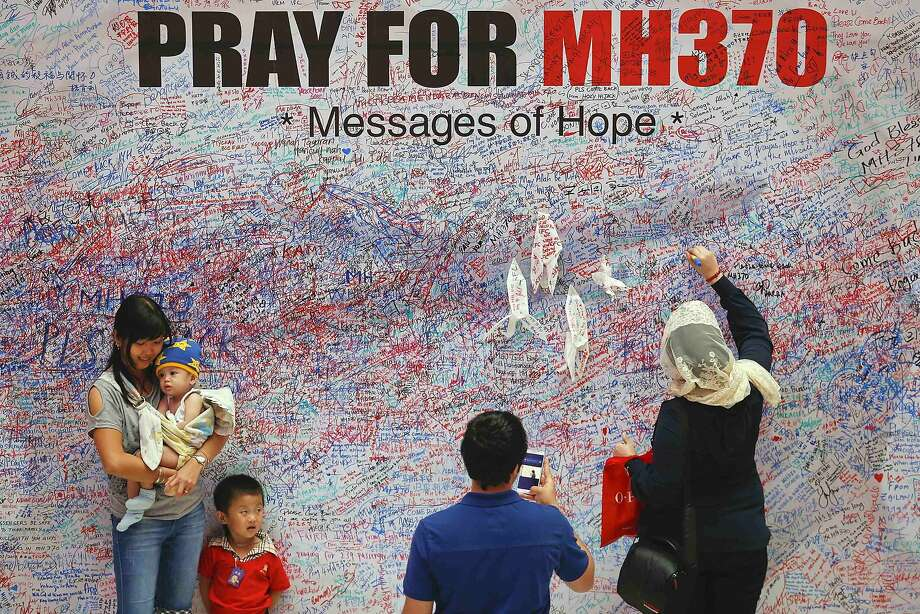 Handwritten messages of support crowd a wall in Kuala Lumpur as the search for the Malaysian jetliner missing since March 8 expands to include Central Asia and the southern Indian Ocean. Photo: Damir Sagolj, Reuters