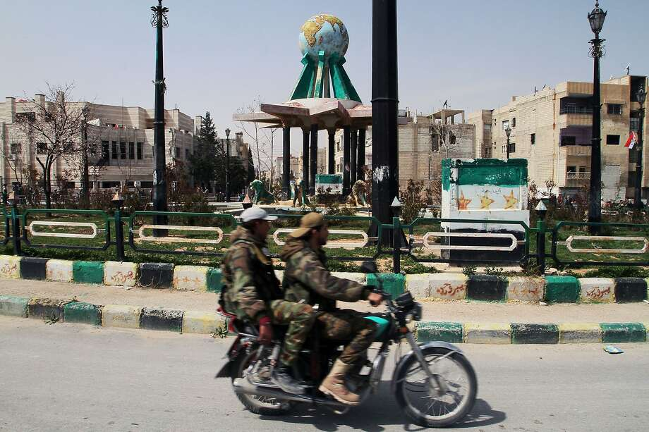 Syrian government forces ride a motorcycle around the main square of Yabroud town near the Lebanon border. The location in the Qalamoun region is strategically important to rebel fighters. Photo: Str, Associated Press