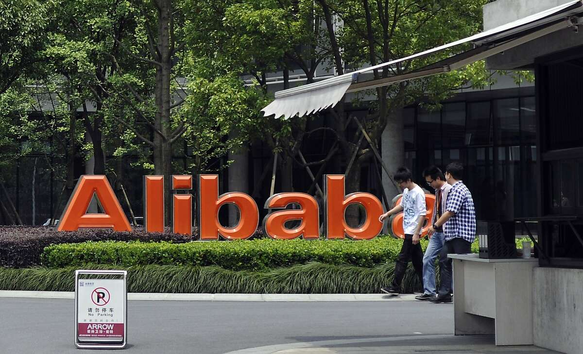 FILE - Young men walk past the corporate logo at the headquarters compound of Alibaba Group in Hangzhou in eastern China's Zhejiang province in this May 21, 2012 file photo. The Chinese e-commerce giant Alibaba says it's gearing up to go public on a U.S. stock exchange in what is likely to be the world's biggest IPO this year. The company said Sunday March 16, 2014 that it has