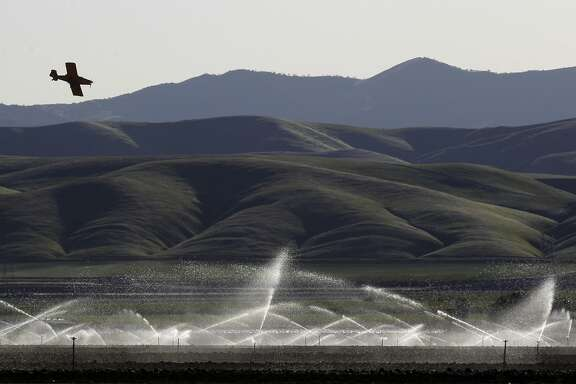 Land is watered as a crop duster works on a field nearby a few miles from the WaterFX desalination plant pilot project in Fresno County near the Panoche Water and Drainage District headquarters in Firebaugh, Calif. The demonstration plant uses solar troughs and Concentrated Solar Still technology to desalinate waste water provided by the Panoche Water and Drainage District. Mandell hopes to eventually build a plant that can process 2 million gallons of water a day, water that is sorely needed in the valley.