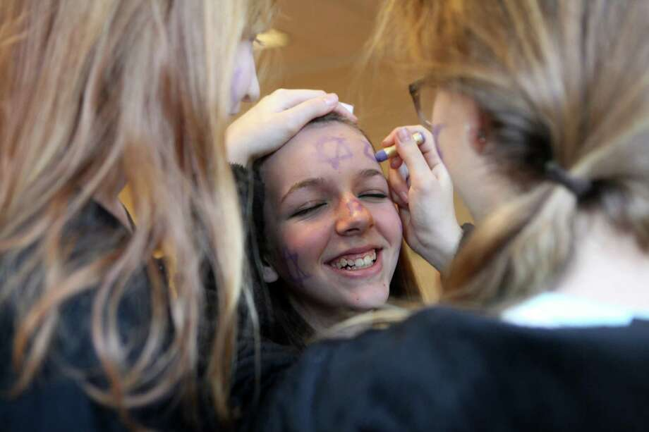 Michele Greenberg, 9, left, and Rebecca Greenberg, 13, right, paint the face of Amanda Katz, 14, at a Purim festival of tThe Conservative Synagogue of Westport on Sunday, March 16, 2014. Photo: Unknown, B.K. Angeletti / Connecticut Post freelance B.K. Angeletti