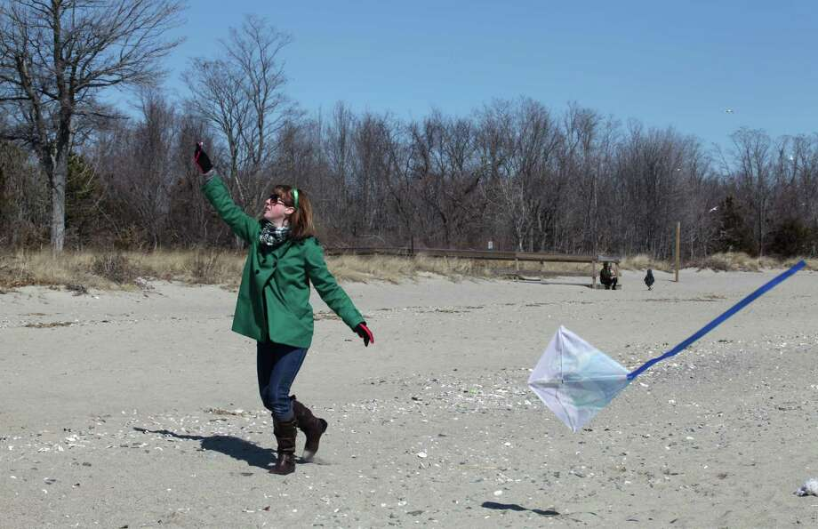 Beth Kassay flies a kite on Walnut beach on Sunday, March 16, 2014. She was there with her children to support her husband, Andrew, who took the Leprechaun Leap to benefit the Literacy Center of Milford. Participants of the leap took a quick dip in the water. Photo: Unknown, B.K. Angeletti / Connecticut Post freelance B.K. Angeletti