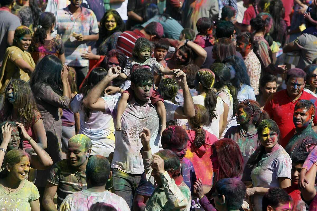 A man holds a little girl on his shoulders during a holi celebration at the Vedic Dharma Samaj Fremont Hindu Temple on March 16, 2014 in Fremont, Calif. The Hindu celebration which features people throwing brightly colored powders at one another has become increasingly popular among different groups.