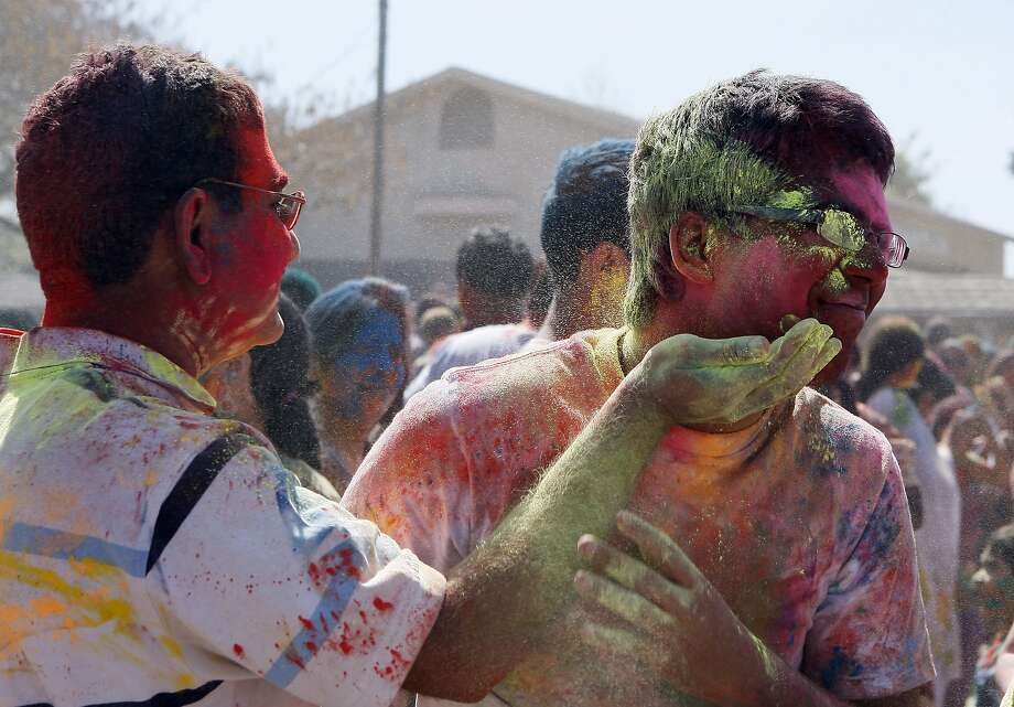 Aakash Gorg (right) tries to dodge Vivet Kaspoor (left) during a Holi celebration at the Vedic Dharma Samaj Fremont Hindu Temple on March 16, 2014 in Fremont, Calif. The Hindu celebration which features people throwing brightly colored powders at one another has become increasingly popular among different groups. Photo: Codi Mills, The Chronicle