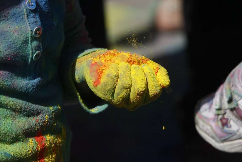 Aarya Shetty, 5, holds a handful of color during a Holi celebration at the Vedic Dharma Samaj Fremont Hindu Temple on March 16, 2014 in Fremont, Calif. The Hindu celebration which features people throwing brightly colored powders at one another has become increasingly popular among different groups. Photo: Codi Mills, The Chronicle