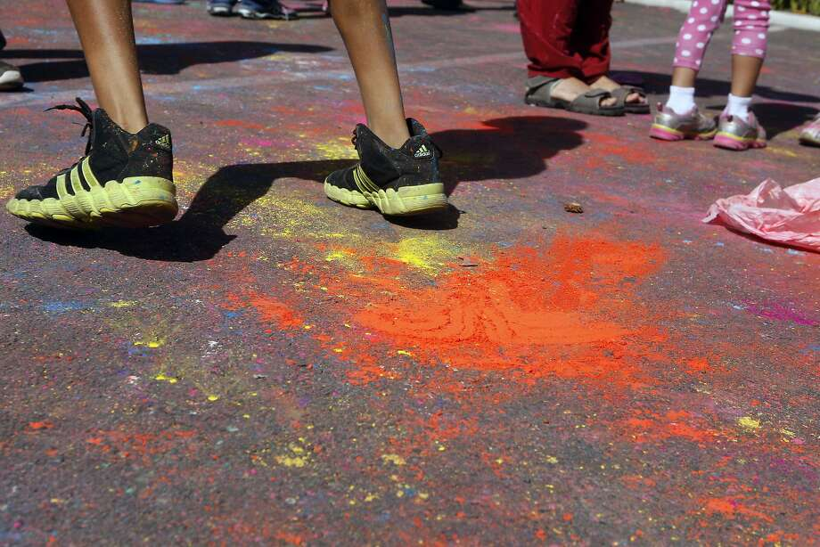 A person walks past a splash of colored powered on the ground during a Holi celebration at the Vedic Dharma Samaj Fremont Hindu Temple on March 16, 2014 in Fremont, Calif. The Hindu celebration which features people throwing brightly colored powders at one another has become increasingly popular among different groups. Photo: Codi Mills, The Chronicle