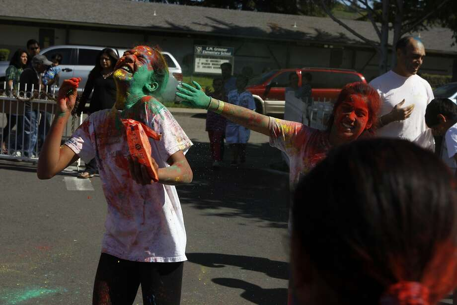 Kayal Rajkumar, 13, (left) has color thrown at her face during a Holi celebration at the Vedic Dharma Samaj Fremont Hindu Temple on March 16, 2014 in Fremont, Calif. The Hindu celebration which features people throwing brightly colored powders at one another has become increasingly popular among different groups. Photo: Codi Mills, The Chronicle
