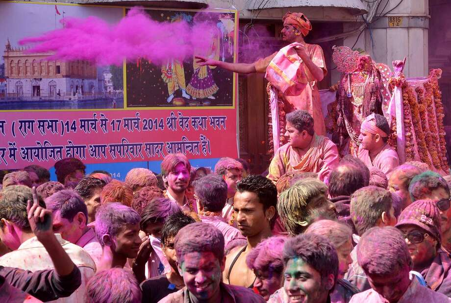 Indian devotees covered with coloured powder carry an idol of Lord Krishna (R) during Holi celebrations at the Durgiana Temple in Amritsar on March 16, 2014. Holi, the popular Hindu spring festival of colours, is observed in India at the end of the winter season on the last full moon of the lunar month. AFP PHOTO/NARINDER NANUNARINDER NANU/AFP/Getty Images Photo: Narinder Nanu, AFP/Getty Images