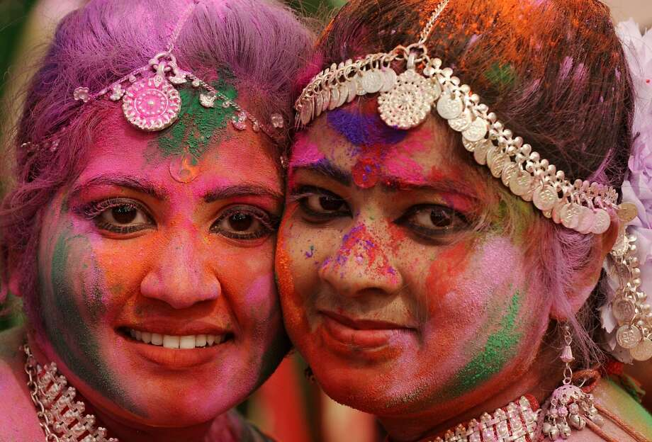 TOPSHOTS- Indian revellers covered with coloured powder pose for a photograph during celebrations for the Holi festival in Siliguri on March 16, 2014. Holi, the Festival of Colours, is a popular Hindu spring festival observed in India and Nepal at the end of winter season on the last full moon day of the lunar month. AFP PHOTO / Diptendu DUTTADIPTENDU DUTTA/AFP/Getty Images Photo: Diptendu Dutta, AFP/Getty Images