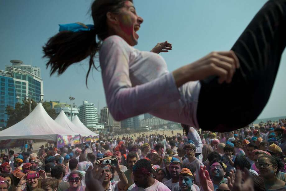 A woman is thrown in the air as revellers take part in Holi celebrations organised by members of South Korea's Indian community at Haeundae beach in the southeastern city of Busan on March 16, 2014. Holi, the popular Hindu spring festival of colours, is observed in India at the end of the winter season on the last full moon of the lunar month.    AFP PHOTO / Ed JonesED JONES/AFP/Getty Images Photo: Ed Jones, AFP/Getty Images