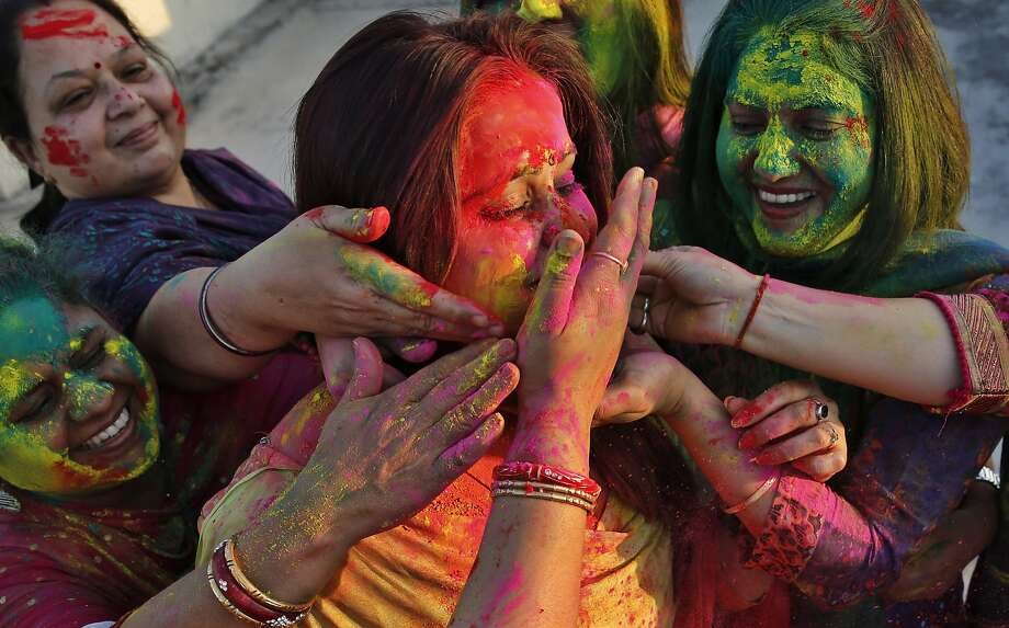 "Indian women smear colors on their faces as they celebrate ""Holi,"" a festival of colors, in Allahabad, India, Sunday, March 16, 2014. The festival heralds the arrival of spring. (AP Photo/ Rajesh Kumar Singh) Photo: Rajesh Kumar Singh, Associated Press"
