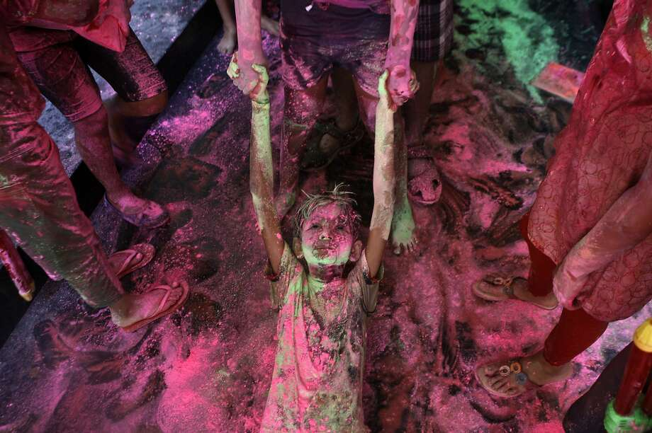 An Indian boy drags another on the floor of an apartment as they play with colors during the Holi festival in Chennai, India, Sunday, March 16, 2014. The festival also marks the advent of spring. (AP Photo/Arun Sankar K) Photo: Arun Sankar K, Associated Press