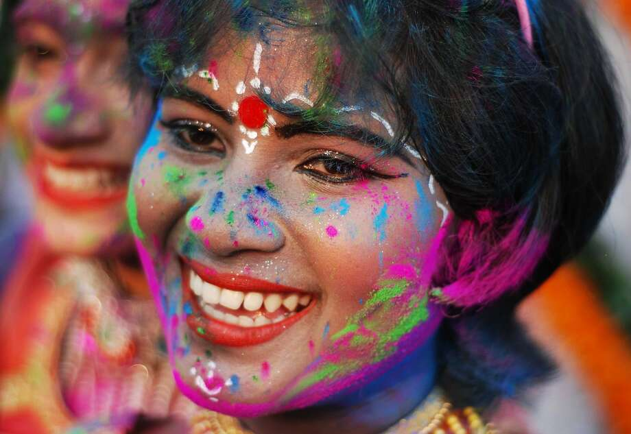 An Indian child adorned with coloured powder takes part in celebrations for the spring festival Holi in Bhubaneswar on March 16, 2014. Holi, the popular Hindu spring festival of colours is observed in India at the end of the winter season on the last full moon of the lunar month.  AFP PHOTO / ASIT KUMARASIT KUMAR/AFP/Getty Images Photo: Asit Kumar, AFP/Getty Images