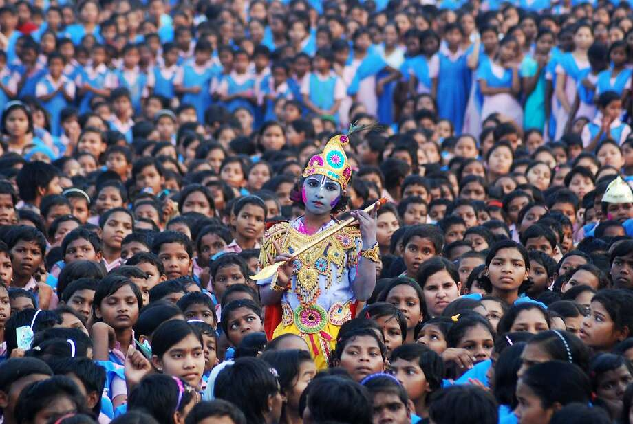 An Indian schoolchild dressed as the Hindu god Krishna and adorned with coloured powder stands among other students during celebrations for the spring festival Holi in Bhubaneswar on March 16, 2014. Holi, the popular Hindu spring festival of colours is observed in India at the end of the winter season on the last full moon of the lunar month.  AFP PHOTO / ASIT KUMARASIT KUMAR/AFP/Getty Images Photo: Asit Kumar, AFP/Getty Images