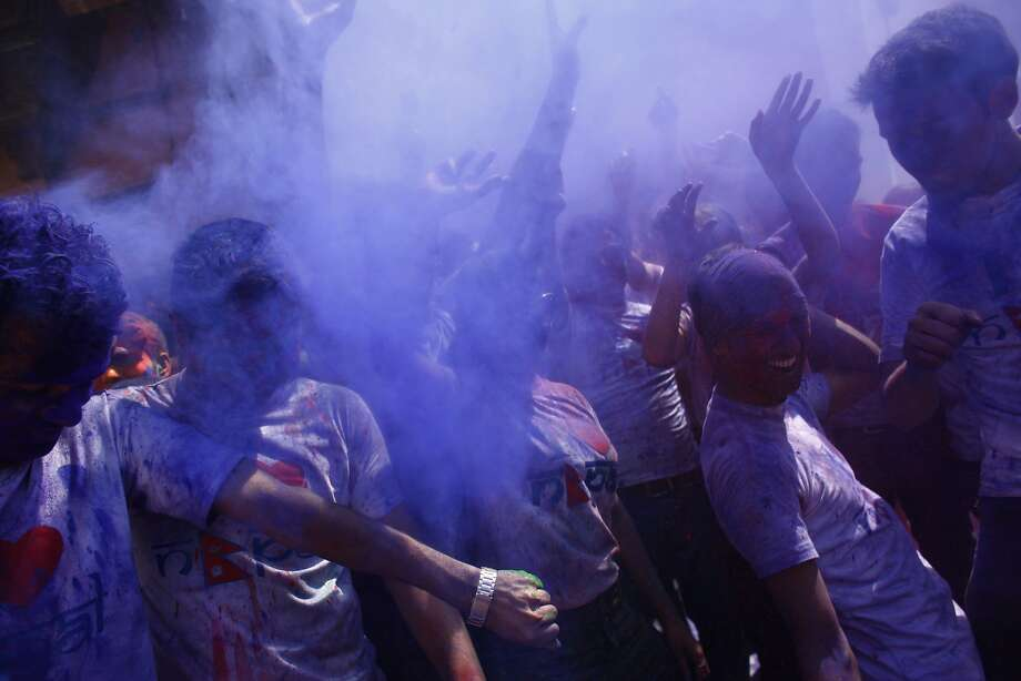 Nepalese people celebrate Holi, the festival of colors with colored powder at the Basantapur Durbar Square, in Katmandu, Nepal, Sunday, March 16, 2014. The festival also marks the advent of spring. (AP Photo/Niranjan Shrestha) Photo: Niranjan Shrestha, Associated Press