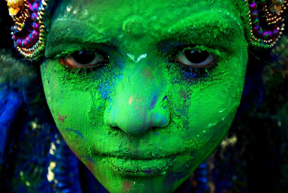 The wearing of the green: An Indian child plastered with colored powder celebrates 