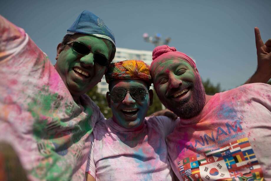 Devotees covered with coloured powder pose for a photo as they take part in Holi celebrations organised by members of South Korea's Indian community at Haeundae beach in the southeastern city of Busan on March 16, 2014. Holi, the popular Hindu spring festival of colours, is observed in India at the end of the winter season on the last full moon of the lunar month.    AFP PHOTO / Ed JonesED JONES/AFP/Getty Images Photo: Ed Jones, AFP/Getty Images