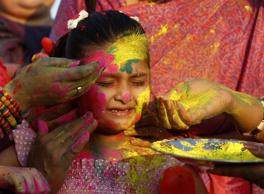 A girl reacts as women smear color on her face to  celebrate Holi, the Hindu festival of colors, in Allahabad, , India, Sunday, March 16, 2014. The festival heralds the arrival of spring. (AP Photo/ Rajesh Kumar Singh) Photo: Rajesh Kumar Singh, Associated Press