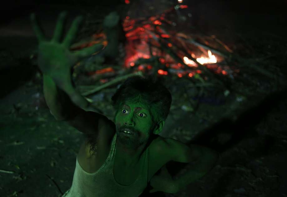An Indian man dances near a bonfire as they celebrate Holi, the Hindu festival of colors, in Allahabad, , India, Sunday, March 16, 2014. The festival heralds the arrival of spring. (AP Photo/ Rajesh Kumar Singh) Photo: Rajesh Kumar Singh, Associated Press