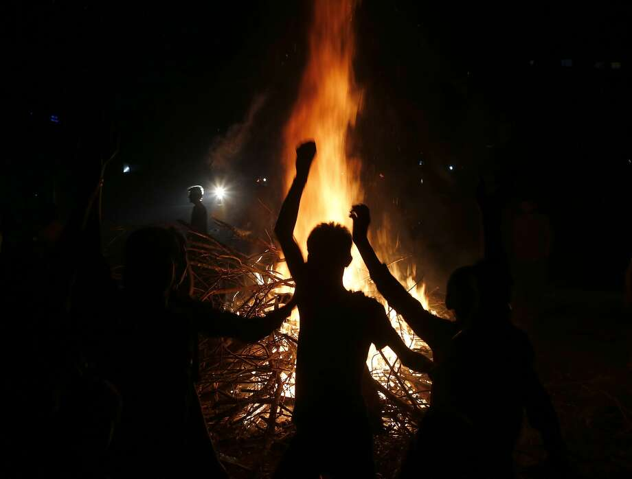 A group of boys dance near a bonfire as they celebrate Holi, the Hindu festival of colors, in Allahabad, , India, Sunday, March 16, 2014. The festival heralds the arrival of spring. (AP Photo/Rajesh Kumar Singh) Photo: Rajesh Kumar Singh, Associated Press