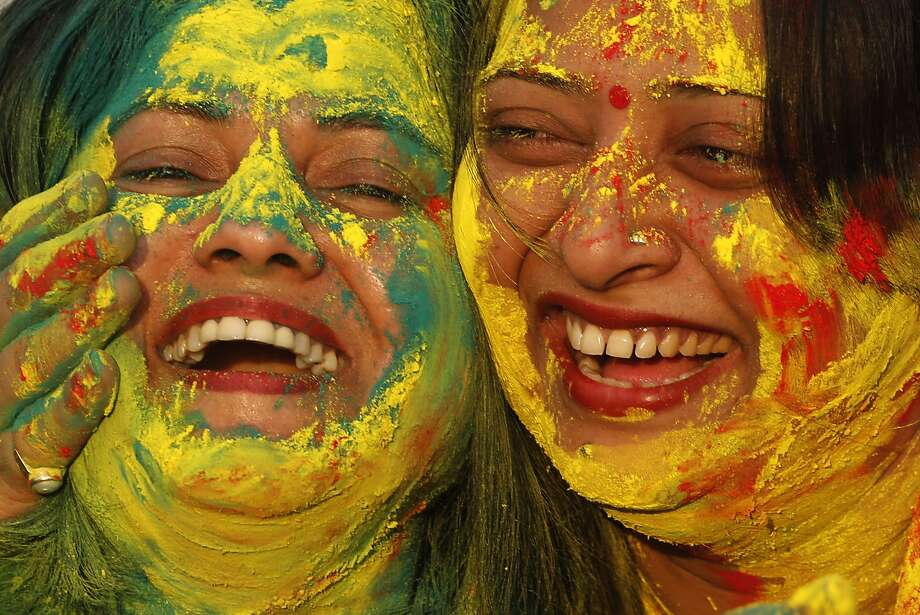 "Indian women smear colors on their faces as they celebrate ""Holi,"" a festival of colors, in Allahabad, India, Sunday, March 16, 2014. The festival heralds the arrival of spring. (AP Photo/Rajesh Kumar Singh) Photo: Rajesh Kumar Singh, Associated Press"