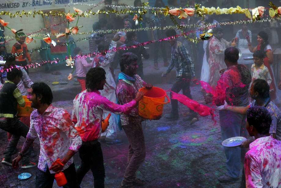 Pakistani Hindus throw coloured water and powder as they take part in celebrations for the Holi festival in Lahore on March 16, 2014. Holi, the popular Hindu spring festival of colours, is observed in Pakistan at the end of the winter season on the last full moon of the lunar month. AFP PHOTO/Arif ALIArif Ali/AFP/Getty Images Photo: Arif Ali, AFP/Getty Images