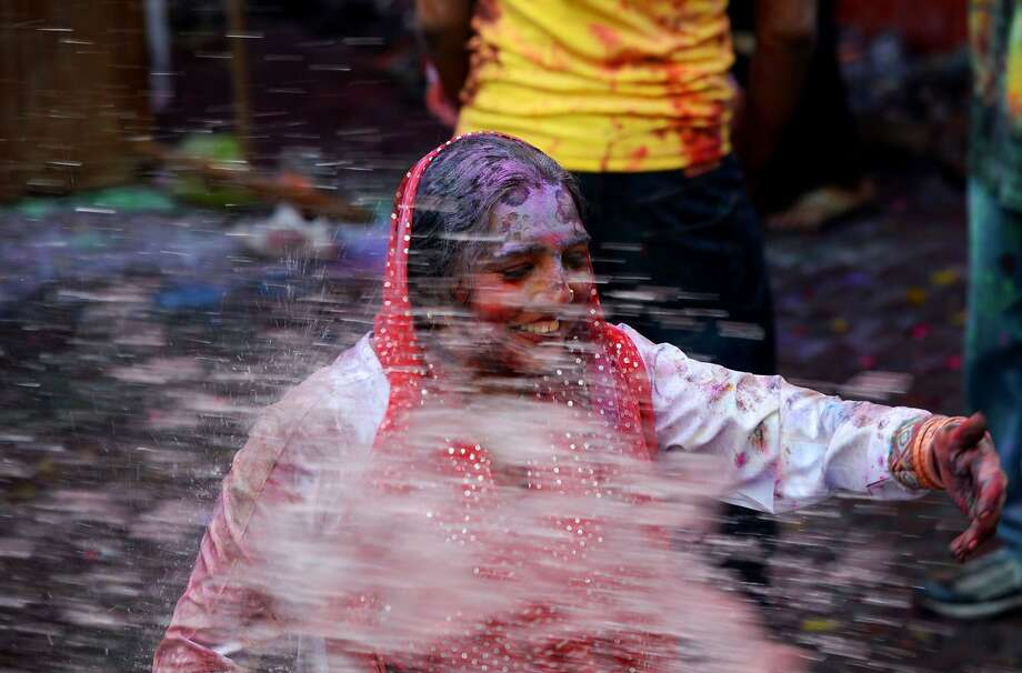A Pakistani Hindu covered with coloured powder is sprayed with coloured water during celebrations for the Holi festival in Lahore on March 16, 2014. Holi, the popular Hindu spring festival of colours, is observed in Pakistan at the end of the winter season on the last full moon of the lunar month. AFP PHOTO/Arif ALIArif Ali/AFP/Getty Images Photo: Arif Ali, AFP/Getty Images