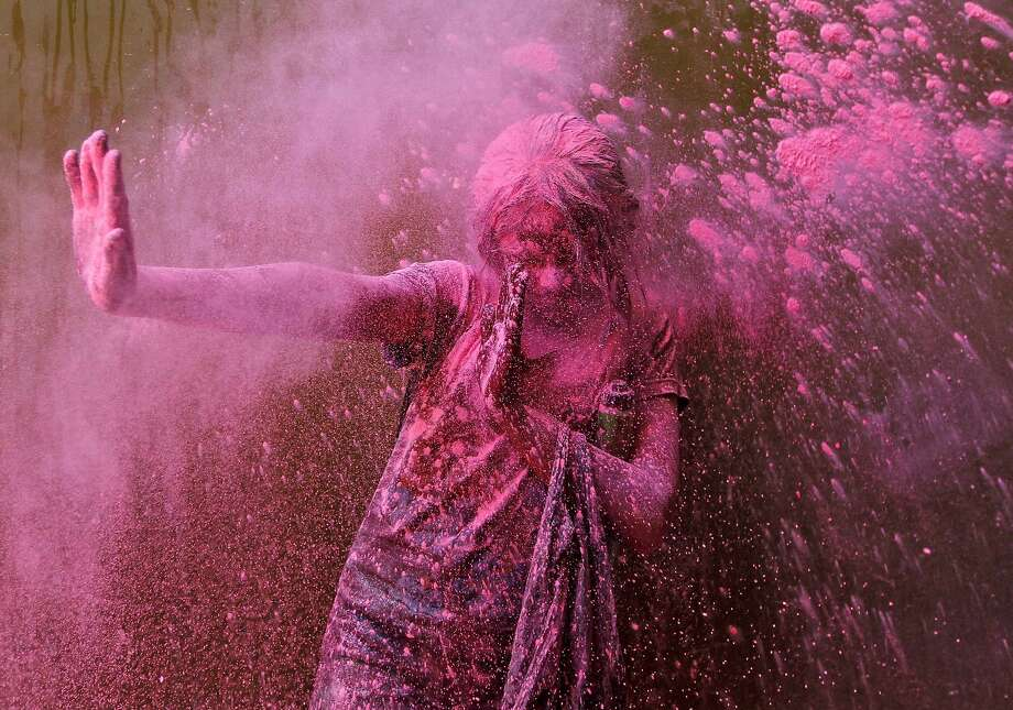 A girl smeared with colours reacts as another girl throws coloured powder at her during Holi celebrations in the southern Indian city of Chennai March 16, 2014. Holi, also known as the Festival of Colours, heralds the beginning of spring and is celebrated all over India. REUTERS/Babu (INDIA - Tags: SOCIETY) Photo: Babu, Reuters