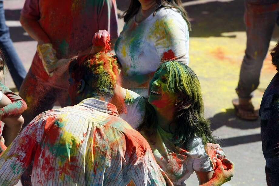 A woman covers a man's head in brightly colored powder during a Holi celebration at the Vedic Dharma Samaj Fremont Hindu Temple on March 16, 2014 in Fremont, Calif. The Hindu celebration has become increasingly popular among different groups. Photo: Codi Mills, The Chronicle