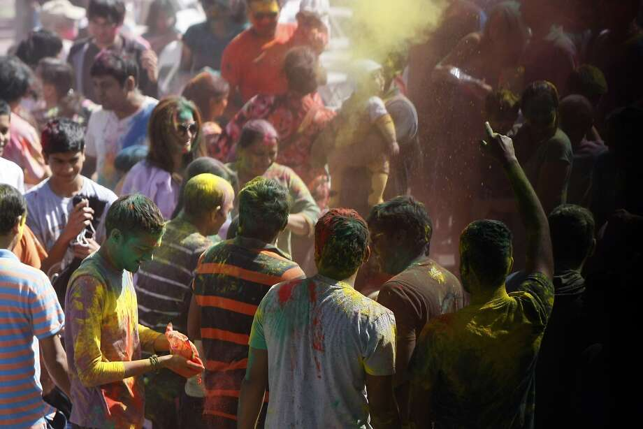 People throw handfuls of color while dancing during a Holi celebration at the Vedic Dharma Samaj Fremont Hindu Temple on March 16, 2014 in Fremont, Calif. The Hindu celebration has become increasingly popular among different groups. Photo: Codi Mills, The Chronicle