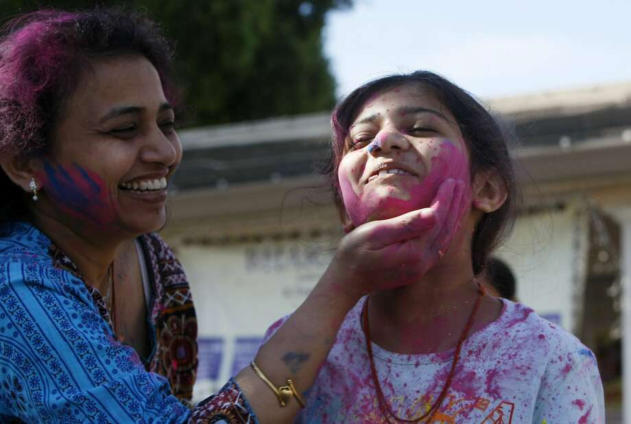 Twinkle Patel smears color on the face of Sallni Patel, 9, (right) during a Holi celebration at the Vedic Dharma Samaj Fremont Hindu Temple on March 16, 2014 in Fremont, Calif. The Hindu celebration which features people throwing brightly colored powders at one another has become increasingly popular among different groups. Photo: Codi Mills, The Chronicle