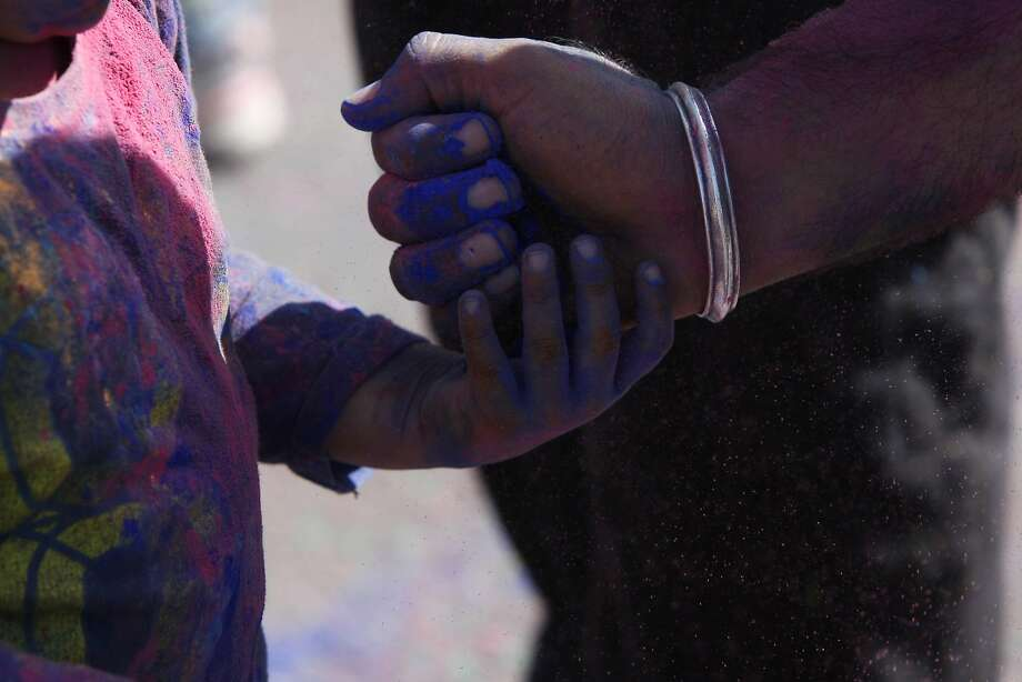 Aaryan Anand, 2, has color poured into his hand by Nitin Anand (right) during a Holi celebration at the Vedic Dharma Samaj Fremont Hindu Temple on March 16, 2014 in Fremont, Calif. The Hindu celebration which features people throwing brightly colored powders at one another has become increasingly popular among different groups. Photo: Codi Mills, The Chronicle