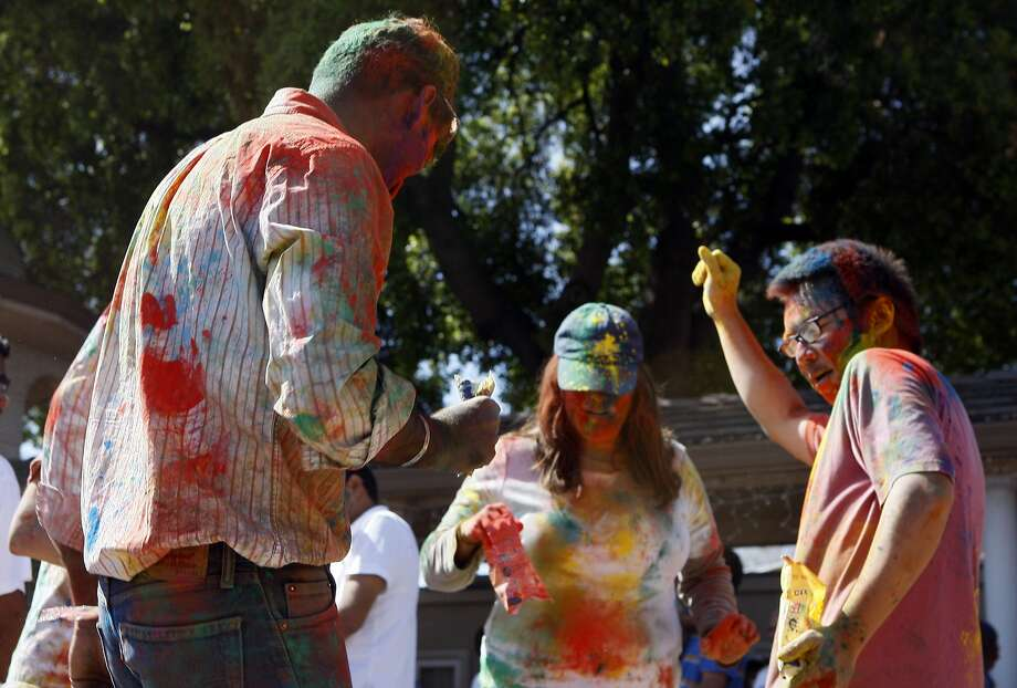 Akshat Jain (left), Rebecca Leung (center), and Carter Leung (right) dance during a Holi celebration at the Vedic Dharma Samaj Fremont Hindu Temple on March 16, 2014 in Fremont, Calif. The Hindu celebration which features people throwing brightly colored powders at one another has become increasingly popular among different groups. Photo: Codi Mills, The Chronicle
